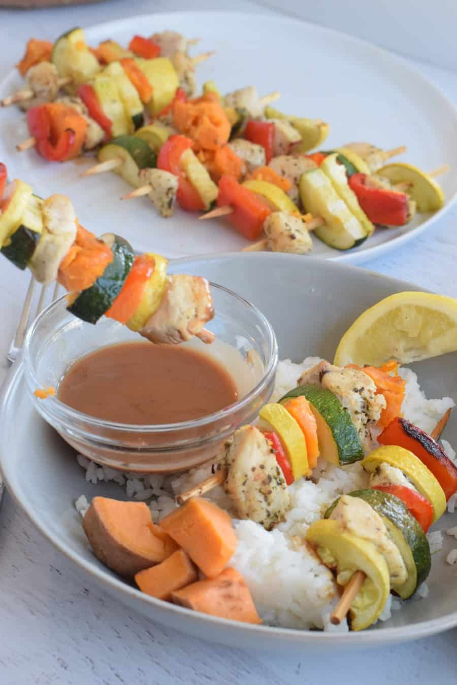 oven baked chicken kabob with veggies dipping in side of balsamic sauce on a blue plate with  white rice