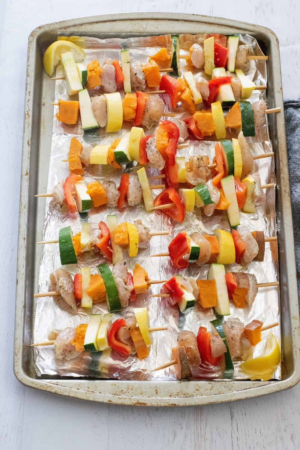 Raw chicken and veggies on skewers before making chicken kabob recipe in oven