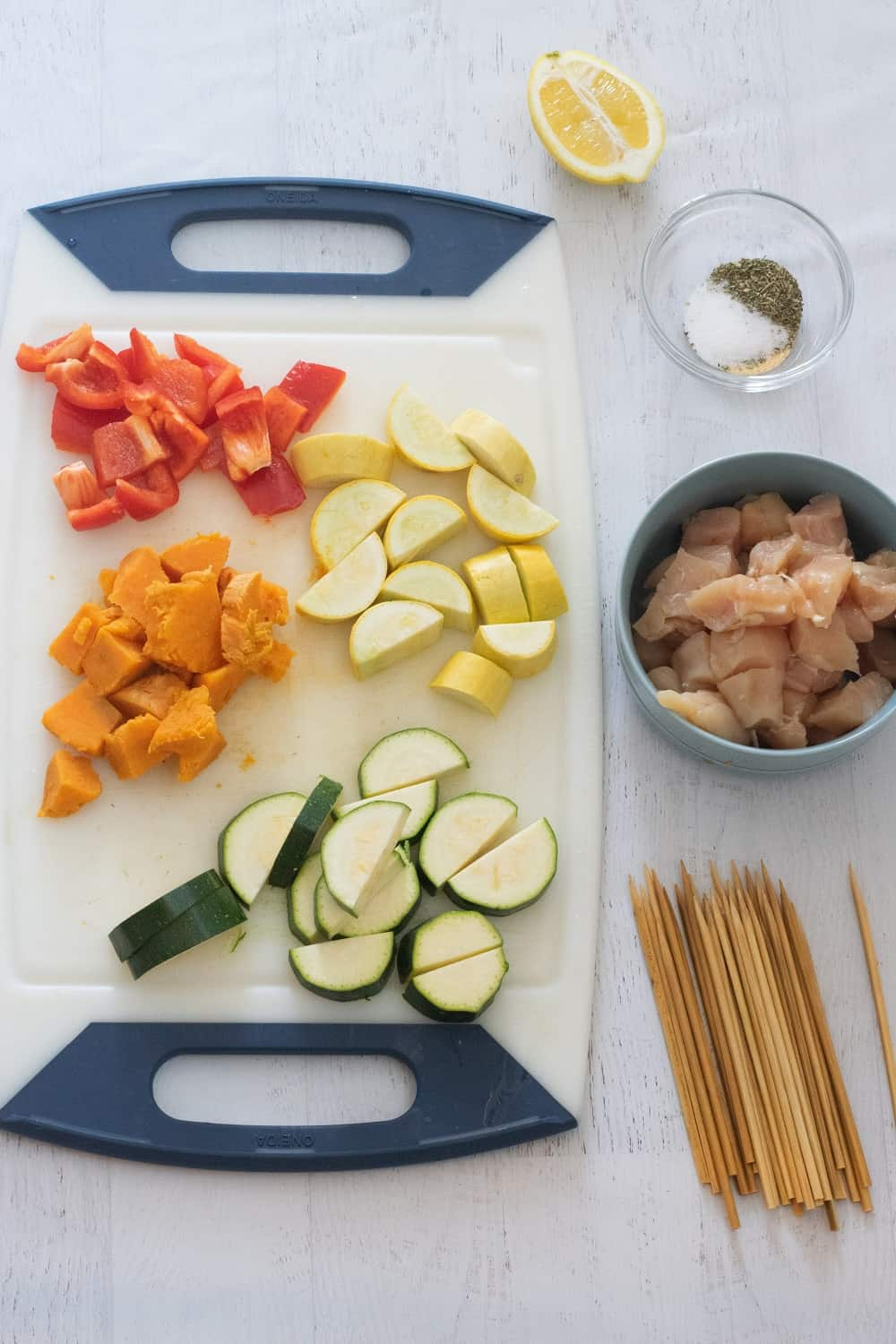 chopped vegetables on white cutting board next to blue bowl with raw chicken to make oven baked chicken kebabs