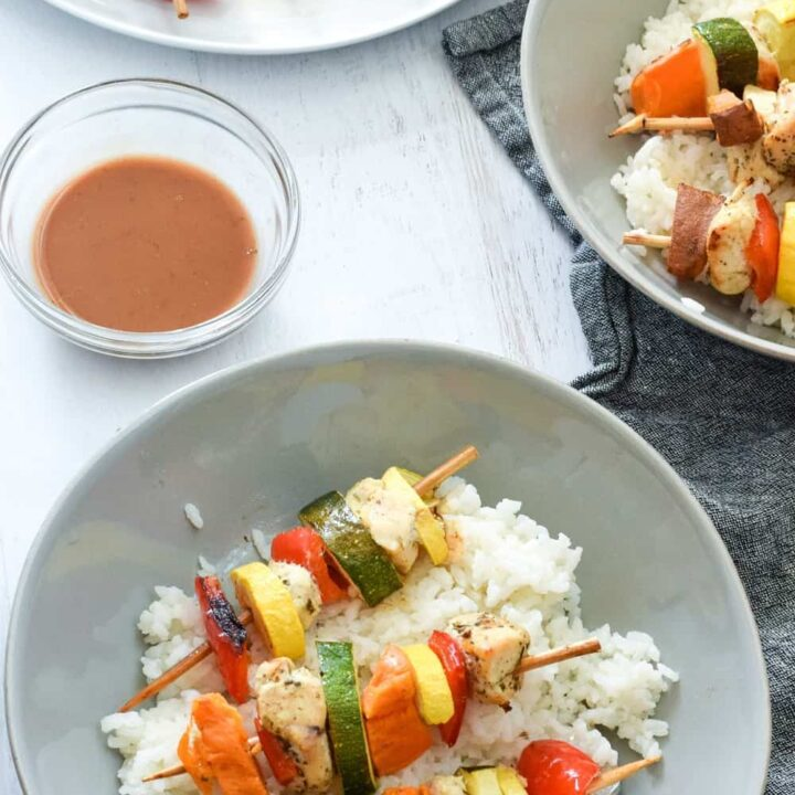 homemade chicken kebabs on white rice on gray bowl