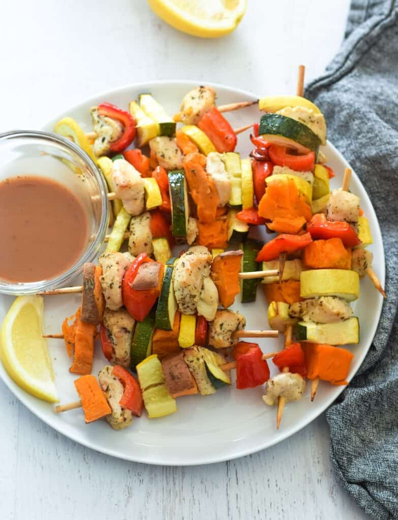 white plate with chicken and sweet potato kebabs on skewers and side of balsamic dipping sauce