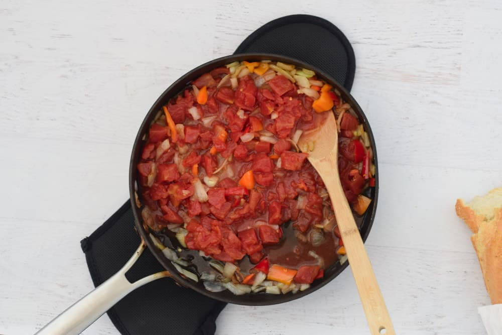 skillet with canned tomatoes being stirred with wooden spoon