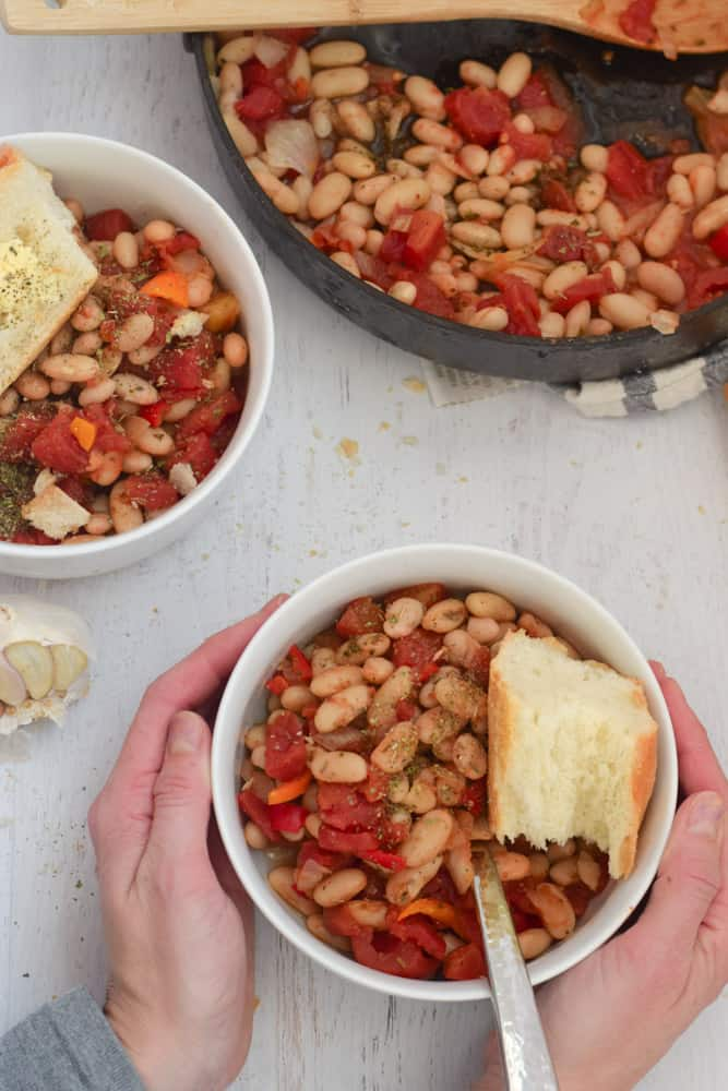Cannellini Bean Skillet Recipe served in white bowl with bread with person holding bowl