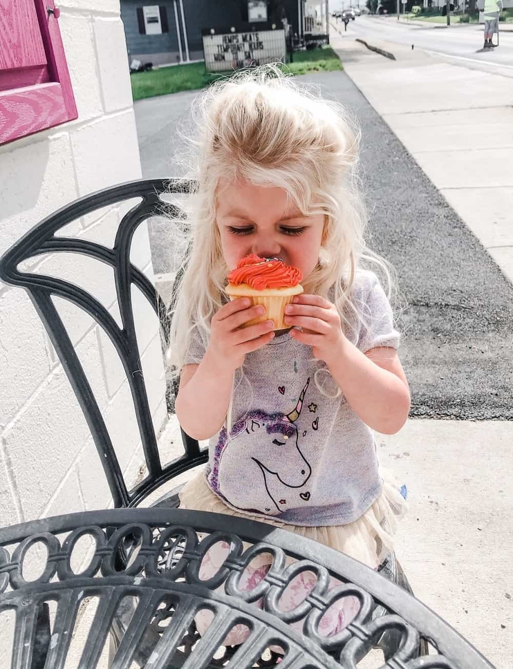 toddler eating cupcake with pink frosting