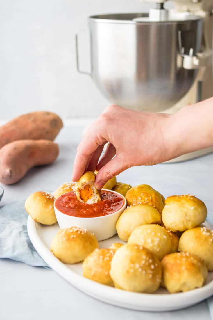 hand dipping sweet potato bite into marinara sauce