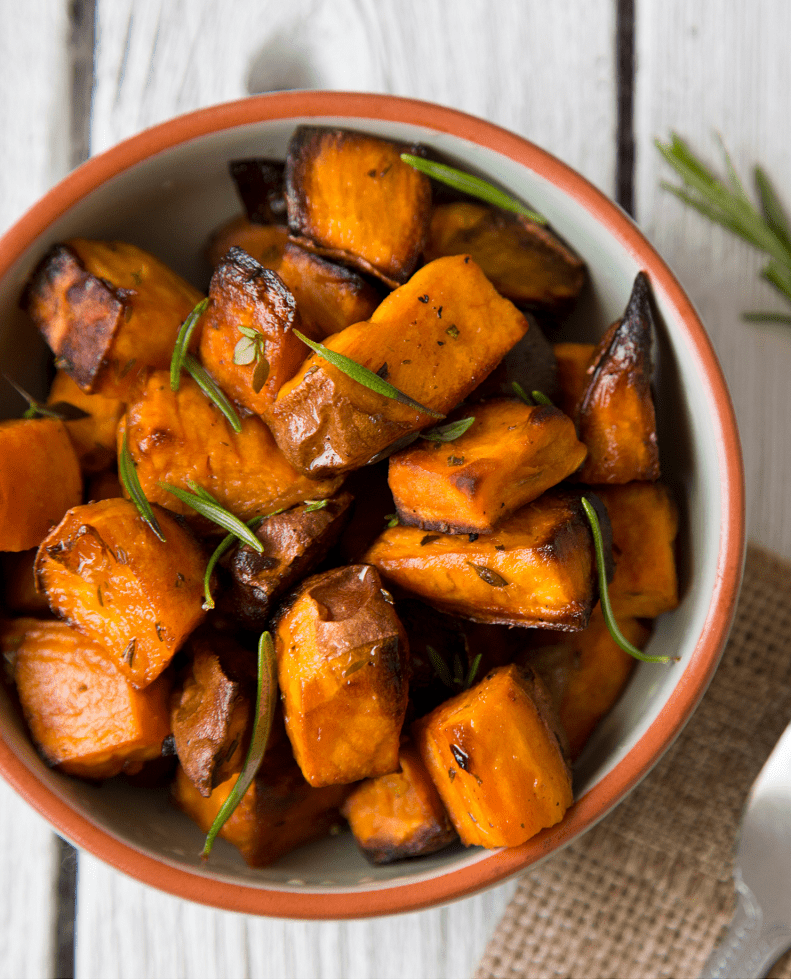 Bowl of sweet potatoes with herbs on top