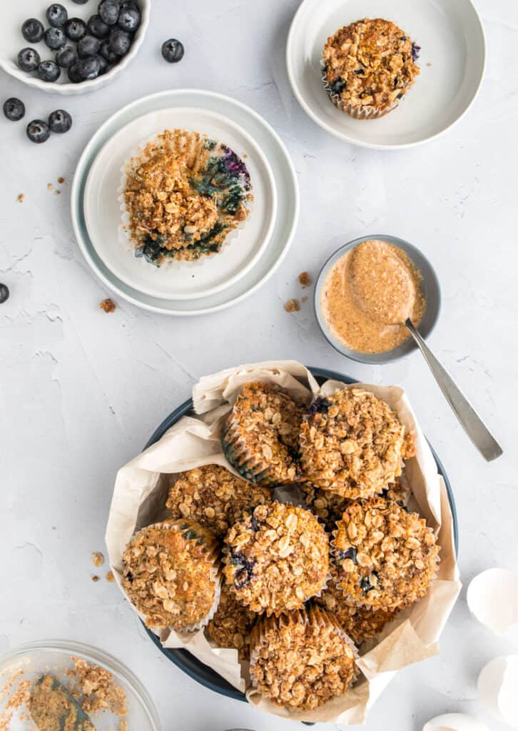 gluten free blueberry muffins in serving bowl with bowl of peanut butter and spoon nearby