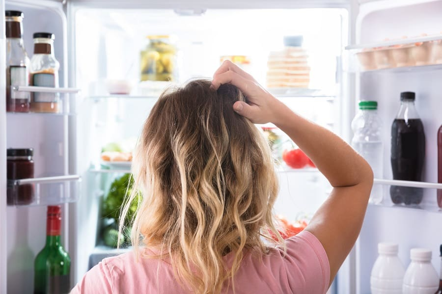 Confused Woman Looking In Open Refrigerator