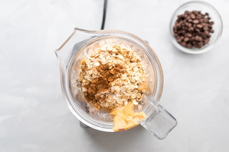 food processor with chickpeas, oats, peanut butter, maple syrup and cinnamon