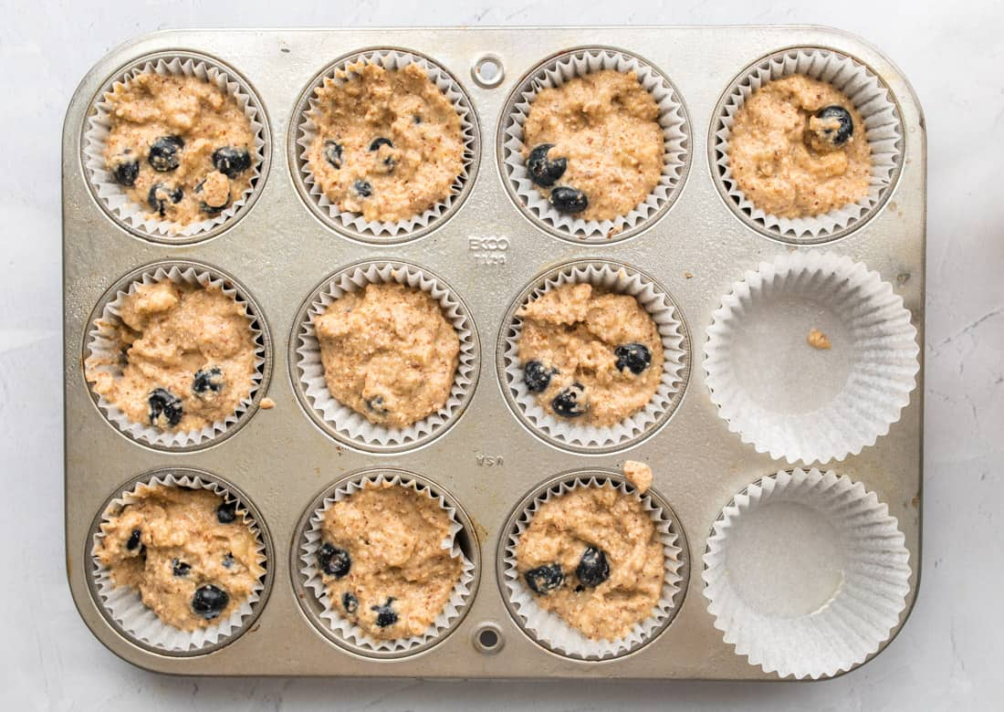 muffin tin with blueberry muffin batter in muffin wrappings