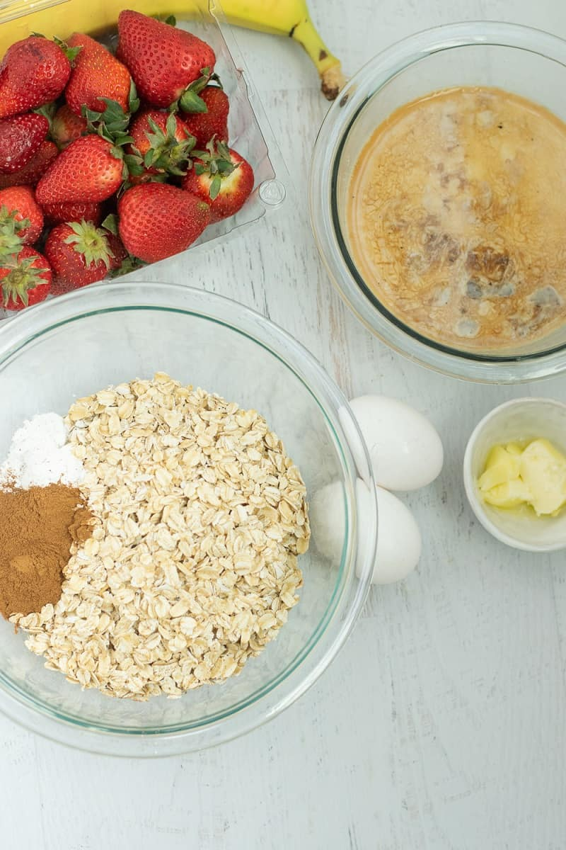 glass bowl of ingredients to make baked oatmeal with strawberries