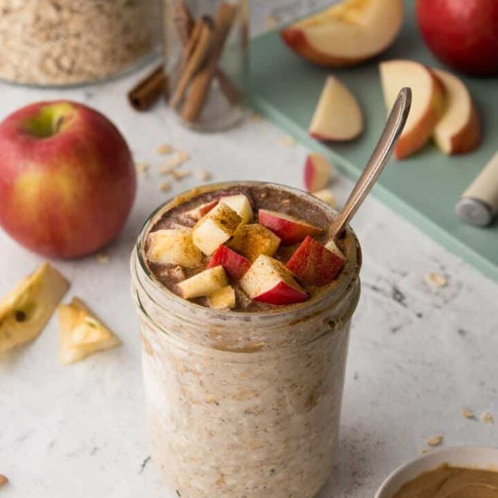 overnight oats in mason jar with apple pie seasoning on countertop with sliced apples in background