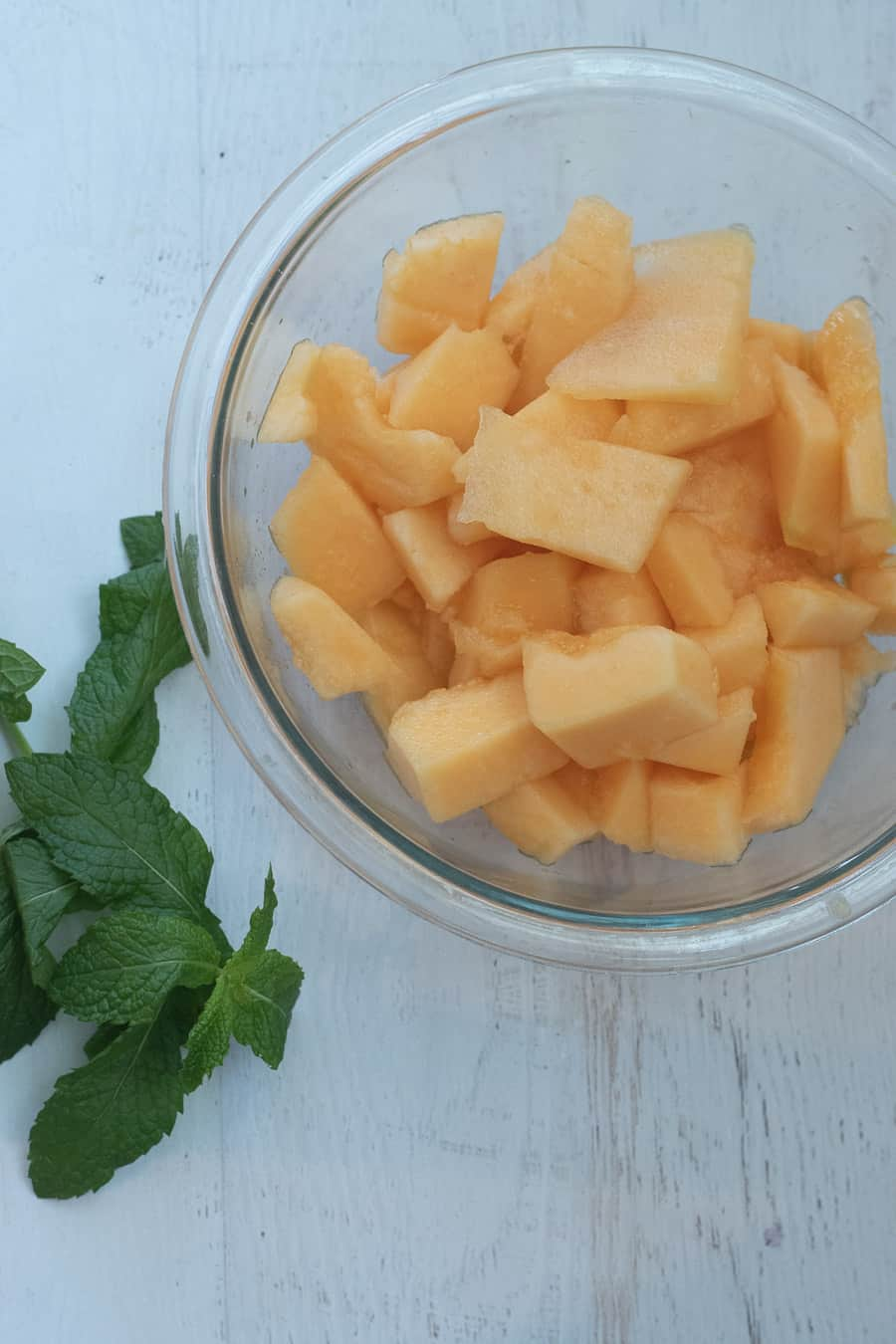 bowl of cantaloupe with mint leaves next to it