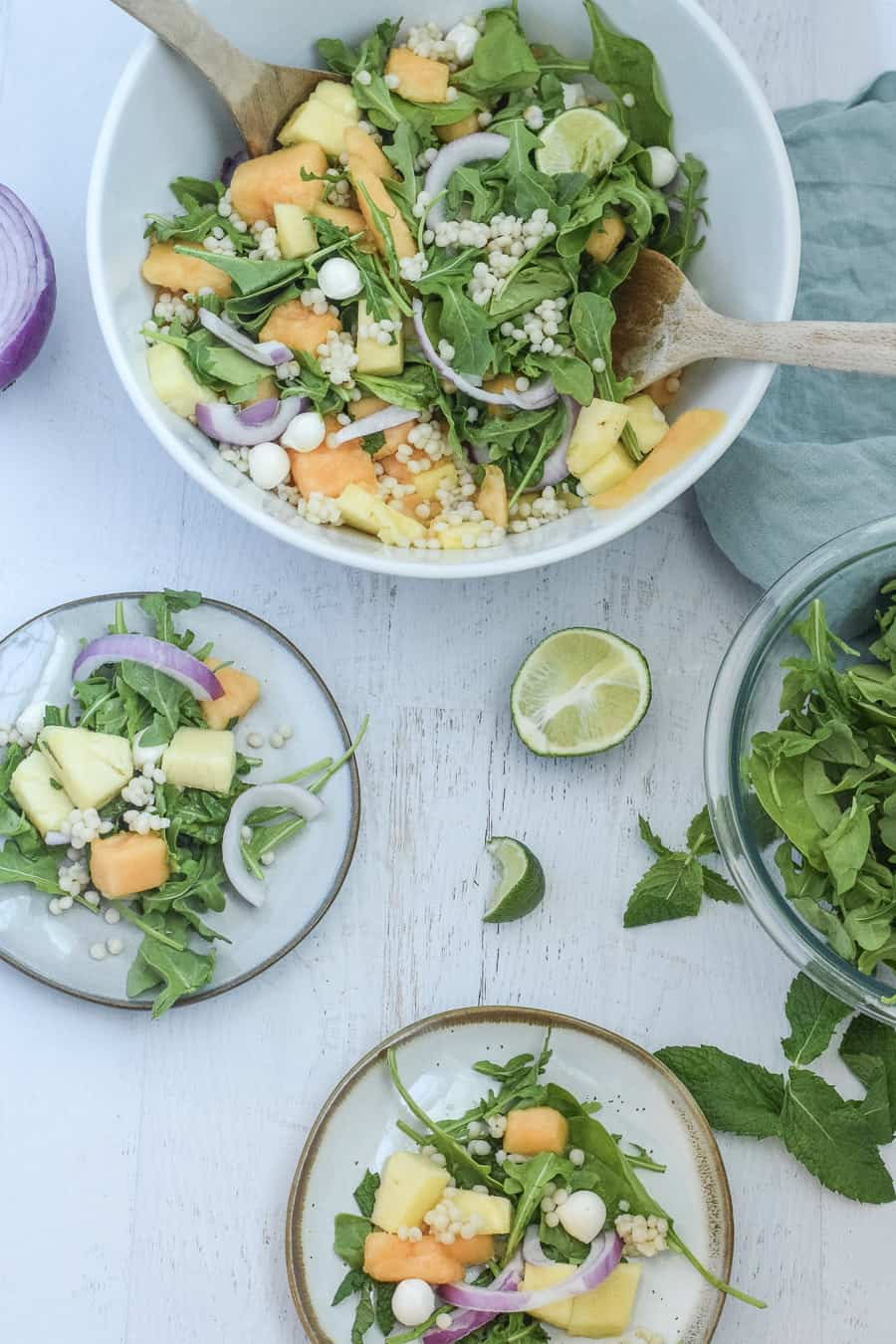 mint cantaloupe salad with mint and pineapple in white serving bowl