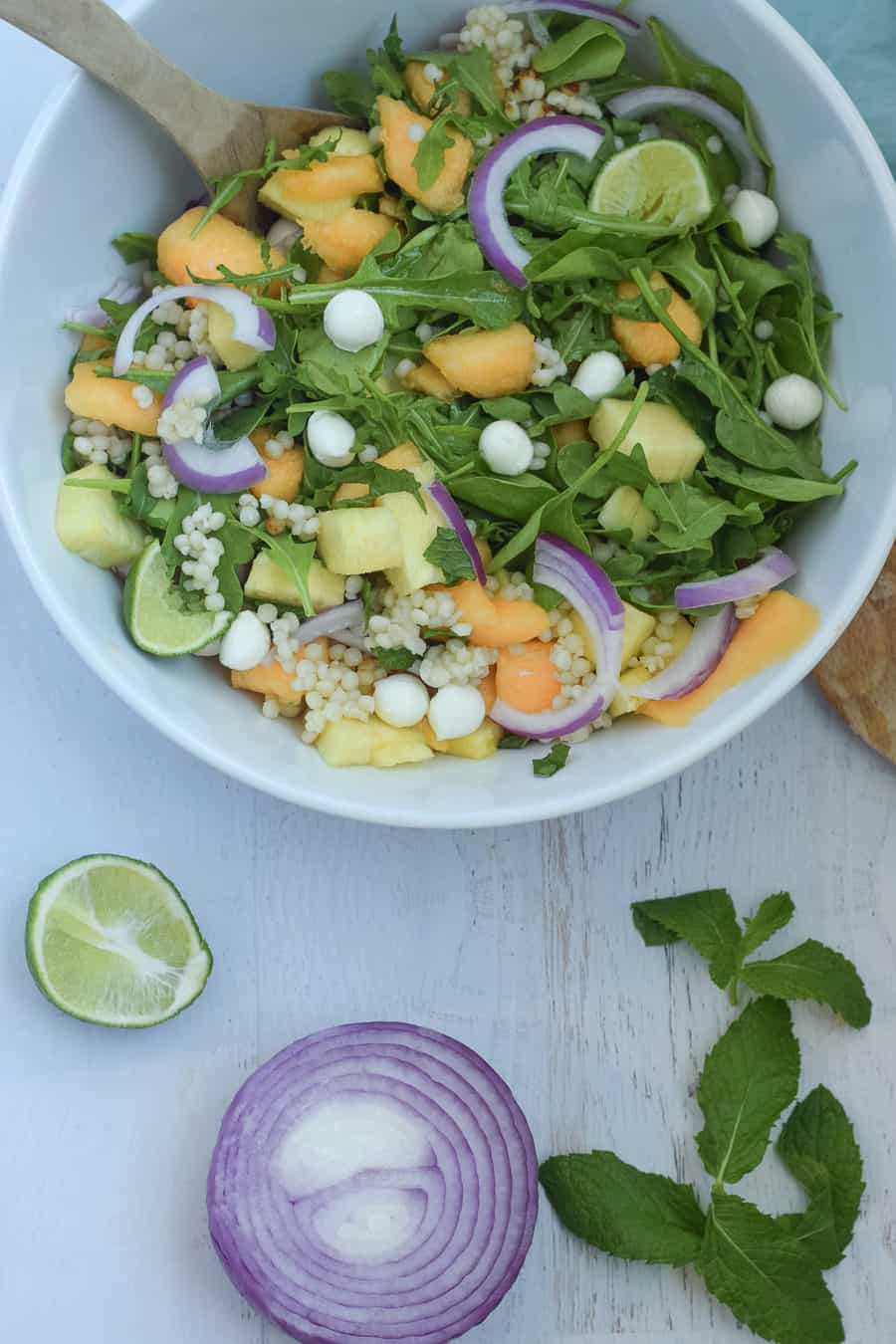 Pineapple mint cous cous salad served in white serving bowl with side of lime and mint